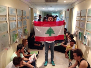 A Lebanese activist holds a national flag in a hallway during a surprise sit-in at Lebanon's environment ministry to demand the minister's resignation after mass protests which began over a nationwide trash collection crisis on September 1, 2015 in the capital Beirut. Several dozen activists are occupying  part of the ministry, hours ahead of a deadline set by campaigners for the government to respond to their demands after a massive weekend demonstration.      AFP PHOTO / STR