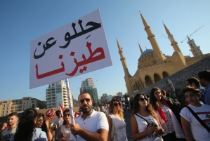 """A Lebanese man holds a placard during a mass rally against a political class seen as corrupt and incapable of providing basic services on August 29, 2015 at the iconic Martyrs Square in Beirut. Waving Lebanese flags, some marked """"We've had enough"""", men, women and children gathered at the square which sat on a Christian-Muslim dividing line during Lebanon's 1975-1990 civil war. The writing in Arabic read: """"Buzz off"""". AFP PHOTO / STR"""