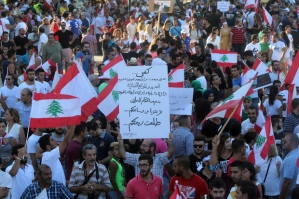"""Lebanese activists hold placards and wave their national flags during a mass rally against a political class seen as corrupt and incapable of providing basic services on August 29, 2015 at the iconic Martyrs Square in Beirut. Waving Lebanese flags, some marked """"We've had enough"""", men, women and children gathered at the square which sat on a Christian-Muslim dividing line during Lebanon's 1975-1990 civil war. The writing in Arabic reads: """"Enough corruption, enough destruction..."""". AFP PHOTO / STR"""